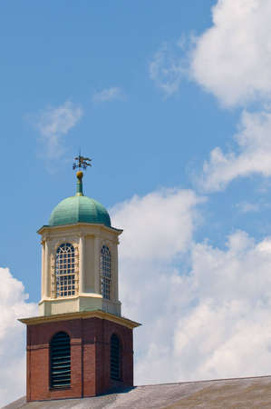 Golden weather vane atop an ornate rooftop tower, with red bricks and white columns photo