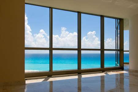 Weergave van tropisch strand via hotel ramen Stockfoto