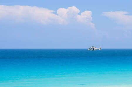 coast guard: Coast guard helicopter hovering above blue and turquoise tropical ocean