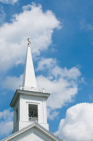 Traditional New England white church steeple against cloudy blue sky