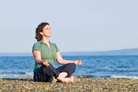 Young brunette woman meditating on the beach, yoga pose, sitting on pebbles photo
