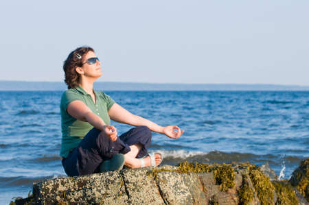 Young brunette woman with sunglasses meditating on the beach, yoga pose, sitting on rock photo