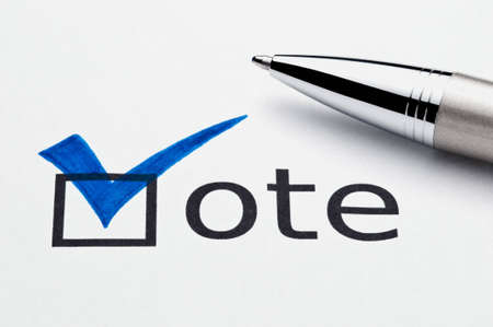 Blue checkmark on vote checkbox, pen lying on ballot paper. Concept for voter registration and participation in elections, or for voting bluedemocrat; not an isolation, paper texture is visible photo