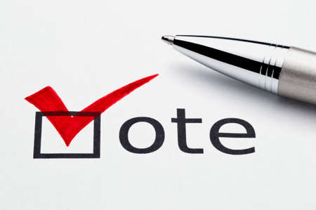 voter: Red checkmark on vote checkbox, pen lying on ballot paper. Concept for voter registration and participation in elections, or for voting redrepublican; not an isolation, paper texture is visible