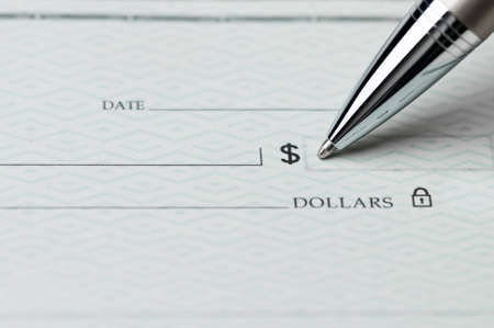 Closeup of ballpoint pen writing on a blank bank check, ready to fill in the dollar amount; selective focus on the tip of the pen Stock Photo