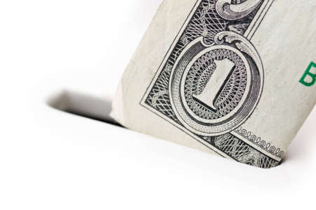 Closeup of one dollar bill going into piggy bank, focus on the bill, very shallow DOF; isolated on white background photo
