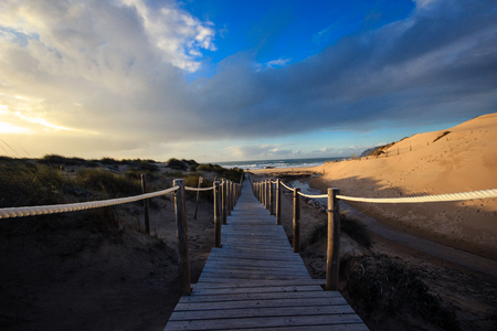 Wooden path to the beach on the dunes. Stock Photo