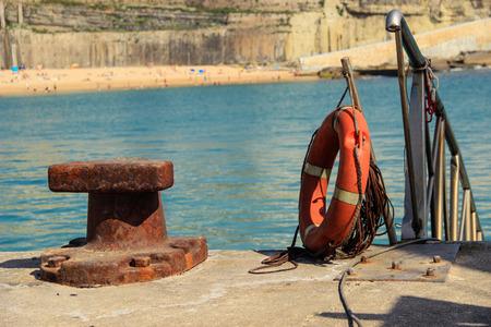 Old rusty steel mooring bollard pole and a Life buoy on a pier