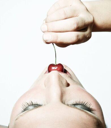 Obere Ansicht einer Frau Verkostung A Cherry Im Gegensatz