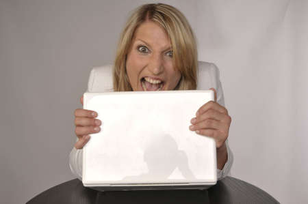 Photo Of An Angry Blond Woman With Laptop photo