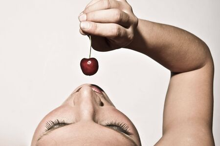 Upper View Closeup Of A Woman Sensually Tasting A Cherry
