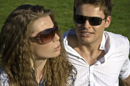 Closeup Of A Couple With Sunglasses Sitting On Grass