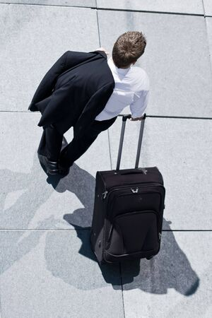Corporate Man With Rolling Luggage Holding His Jacket Stock Photo