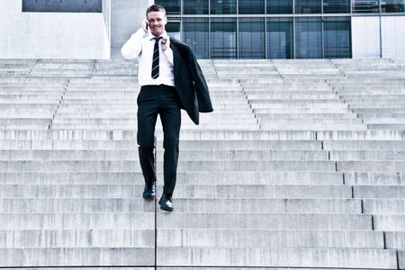 Corporate Man With Cellular Phone Descending On Company Stairs
