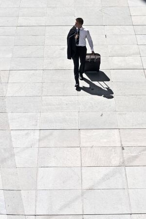 Young Corporate Man With Luggage Walking On Pavement Stock Photo