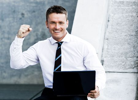 elated: Young Elated Corporate Man With Laptop Showing His Success