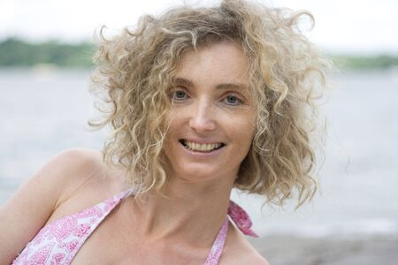 Portrait Of A ältere Blonde Woman With Curly Hair Near Water Side
