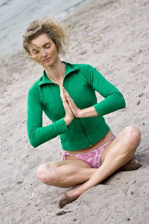 Blond Curly Woman Meditating On Seand Near Water photo