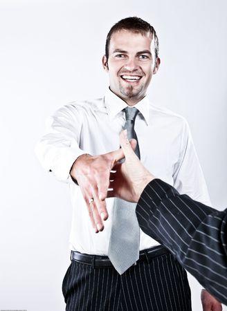 buen trato: Joven hombre corporativo respetuoso agitaci�n manos por un buen trato  Foto de archivo