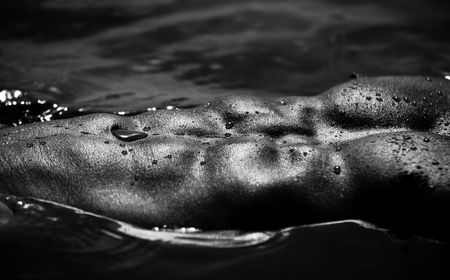 Closeup Monotone  Photo Of A Muscular Male Abdomen And Pecs Shining On Water Stock Photo