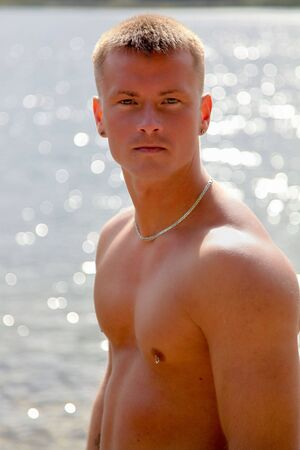 Sexy Young Man Standing In The Sun Near Water photo