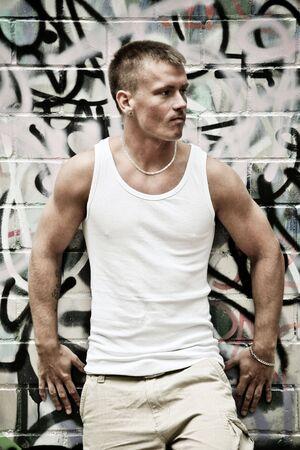 Porträt von Sexy junger Mann In Unterhemd auf Graffiti Wall Hintergrund