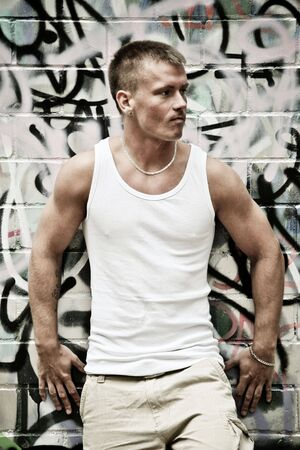 Portrait Of A Sexy Young Man In Undershirt On A Graffiti Wall Background photo