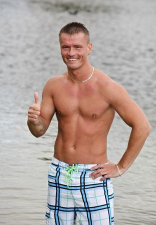 Handsome Athletic Guy Showing The Okay Sign Near Water Stock Photo