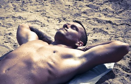 Junge Handsome Man Resting On The Sand After A Swim