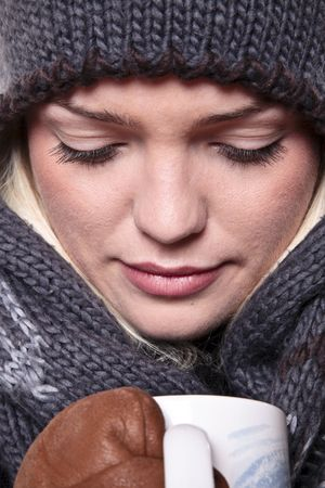 Closeup Portrait Of A Cute Girl Dressed For Winter And Having A Hot Drink photo