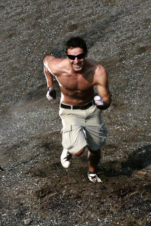 Handsome Athletic Guy Running Without Shirt Up A Hill