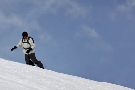 Single Snowboarder Having A Drift On A Blue Sky Background