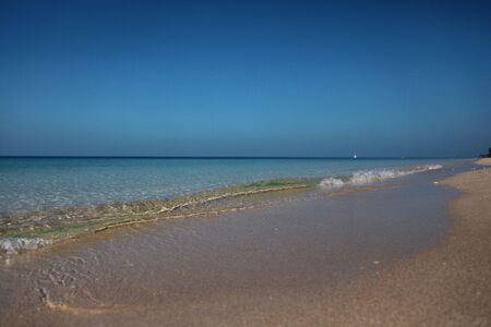 Clear Waves On Shore On A Deep Blue Sky Background With A Ship At The Horizon Standard-Bild