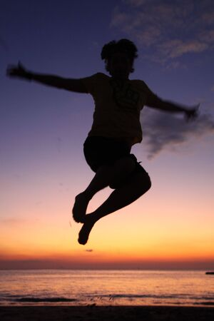 Happy Jumping Silhouette At Dusk On The Beach