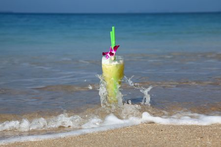 Big Glass Of Cocktail In The Sand And Being Splashed By Waves