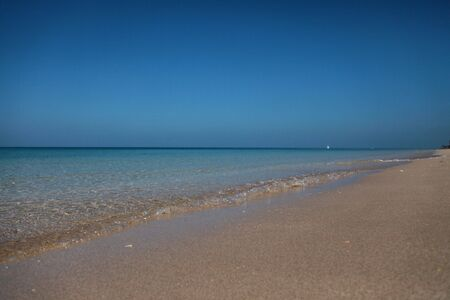 Delicate Sand Shore Washed By Clear Waves With A Ship On The Horizon And A Deep Blue Sky In The Background