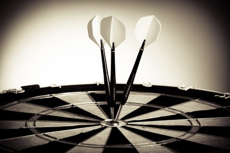 Perspective Photo Of Three Arrows Hitting The Center Of Darts Table
