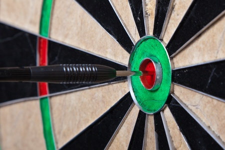 Closeup Image Of An Arrow Straight In The Center Of Darts Board