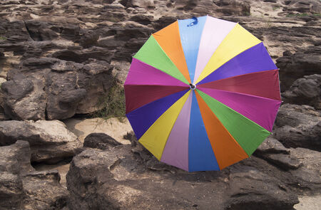 umbrela: colorful umbrella on rock background in Sampanbok of Maekong river, Thailand Stock Photo