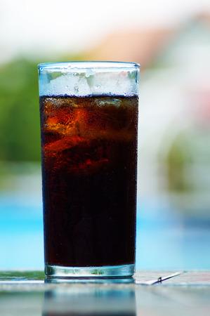 Cola drinking near swimming pool photo