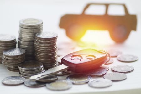 concept car: pile of money coins and key, concept in insurance,loan,finance and buying car background