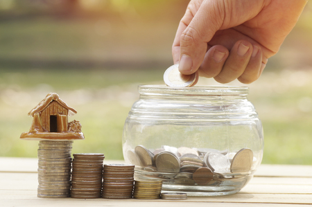 womens hand put money coins in glass bottle for save and donation concept for buying house on wood table, green garden background Stock Photo