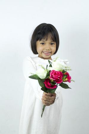 girl holding flower: cute young girl holding flower on soft white background