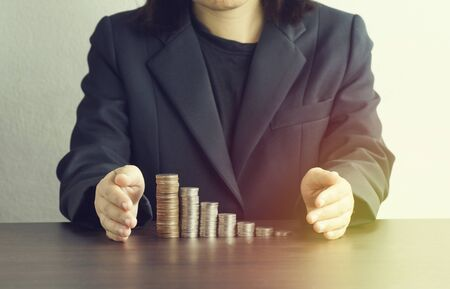 protect money: businesswomen put hand to protect money and business on desk Stock Photo