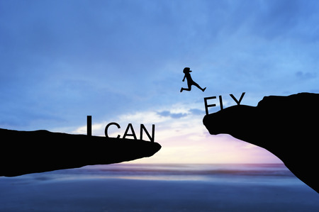silhouette people jumping over the rock with word I can fly Stock Photo