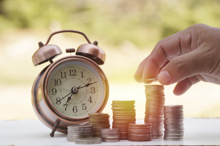 hand put money on pile of coins with clock, concept in time to success in bussiness, finance, bank and account Stock Photo