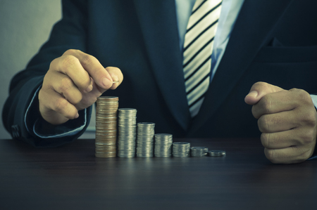 hand of businessman  put money on pile of coins, concept in time to success in bussiness, finance, bank and account Stock Photo