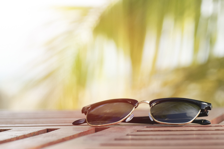 sunglasses on wood table at beach with coconut tree background Stock Photo