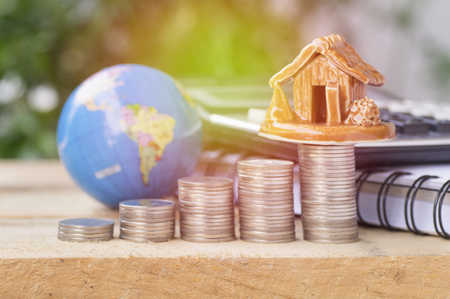 residential construction: pile of coins,globe and home, concept in house finance on wood table Stock Photo