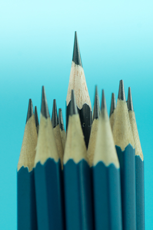 pencils on blue background, concept in leader and standout
